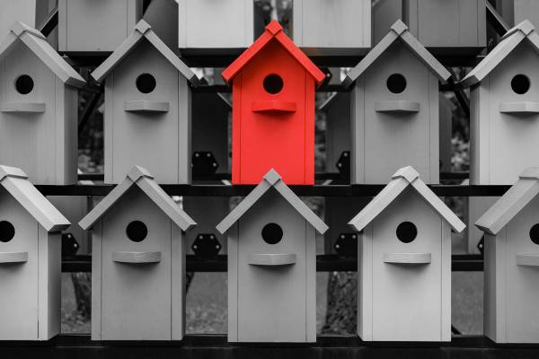 birdhouses, grey with one red.