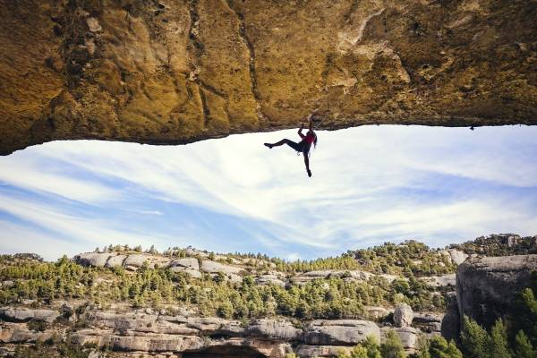 woman rock climber hanging from cliff