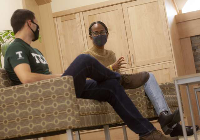 Two students speaking with one another; masked